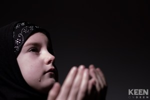 girl sitting down making du'aas and crying