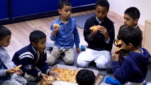 group of boys eating pizza