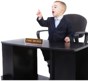 Kid sitting with table and The boss plaque