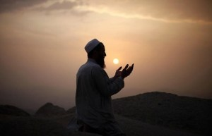 man praying while the sun sets