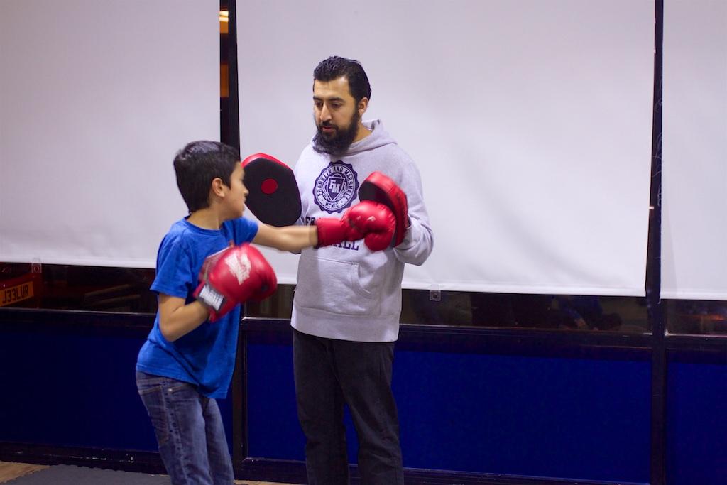 boy punching boxing pad