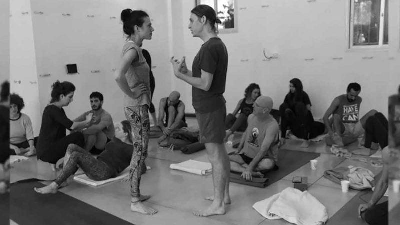 Adam Keen talking to yoga student