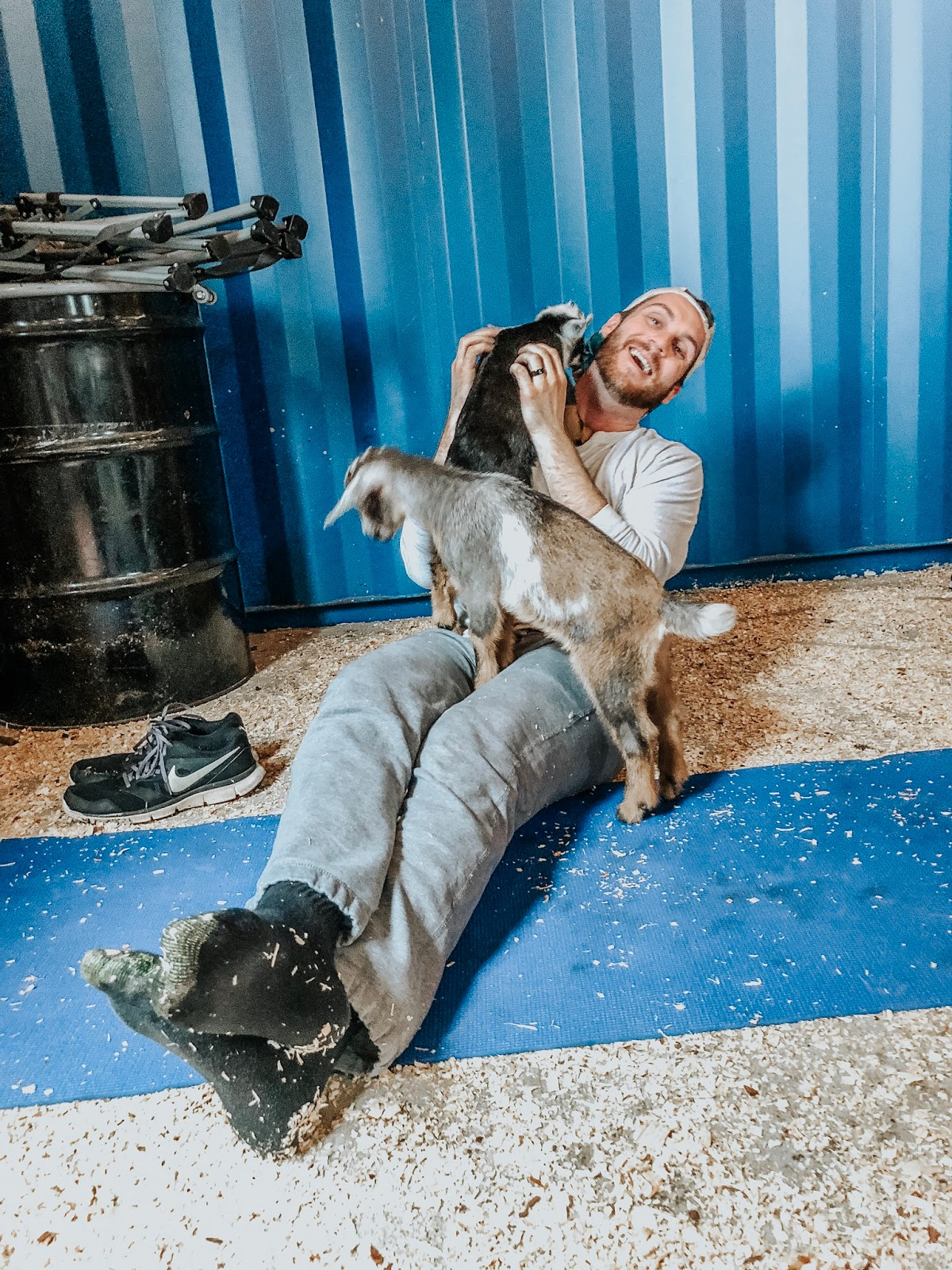 Tampa blogger's husband at Grady Goat Farm in Tampa, Florida taking a goat yoga class