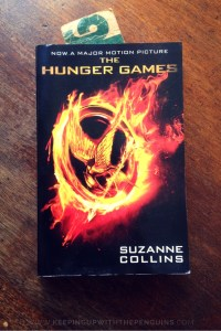 The Hunger Games - Suzanne Collins - book laid on wooden table - Keeping Up With The Penguins