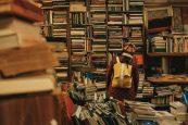 Person Wearing Beanie Looking Through Cluttered Bookshelves