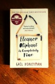 Eleanor Oliphant Is Completely Fine - Gail Honeyman - Book Laid on Wooden Table - Keeping Up With The Penguins