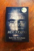 No Friend But The Mountains - Behrouz Boochani - Book Laid On Wooden Table - Keeping Up With The Penguins