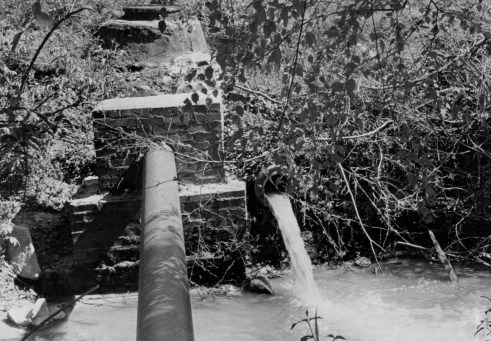 This overflow pipe at Eastway Drive and Briar Creek was spewing raw sewage into the creek in April 1969. Photo: Charlotte Observer archives.