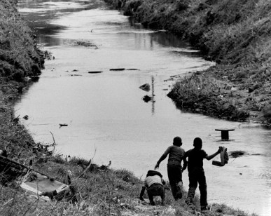 Children play along the bedraggled banks of Irwin Creek in 1968. Photo: Charlotte Observer archives