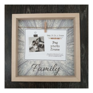 Light wooden photo frame with peg and string, tree background and family text