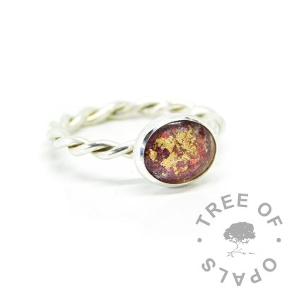 Ashes ring on twisted band with dragon's blood red resin sparkle mix and rose gold leaf. 10x8mm bezel cup and cabochon