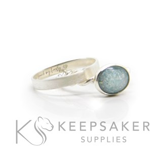 cremation ashes ring and stacking band. Ashes with angelic aqua resin sparkle mix on a twisted band, shown with a brushed stacking band engraved with silver south script font