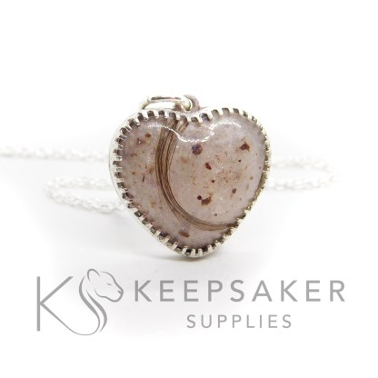 umbilical cord and first curl lock of hair heart necklace with a little white sparkle mix behind the cord and hair. Scalloped setting