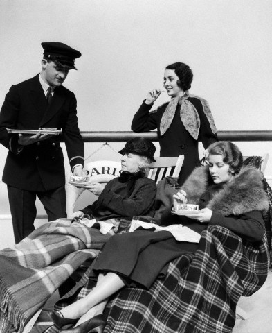 1930s 1920s three women being served tea by a steward on board an ocean liner crossing the atlantic ocean