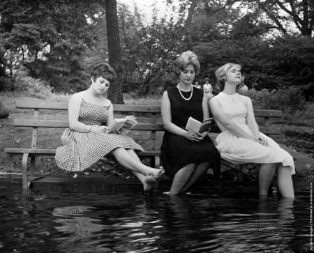 Three women keep cool during a heat wave by moving a park bench into the water in Central Park, New York, 1961