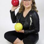 Nainen istuu ja 2 palloa kädessä