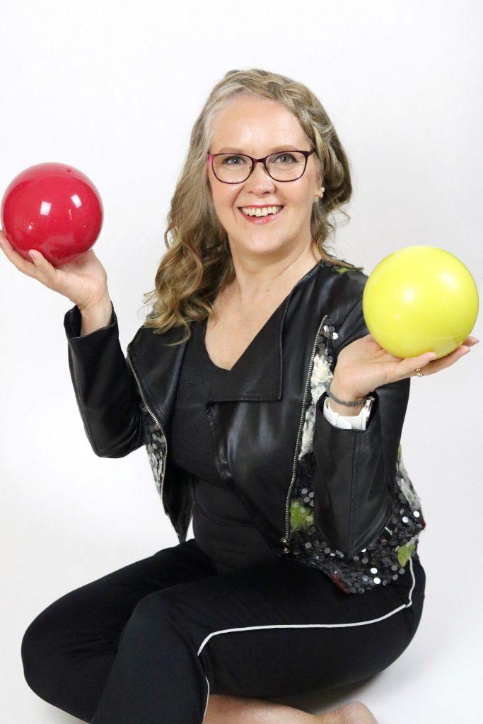 nainen istuu lattialla pallot kädessä