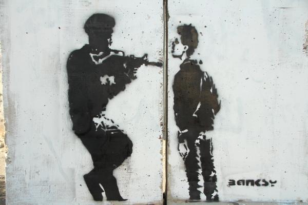 壁の向こう側に行きたい少年と、銃を構えるイスラエル兵