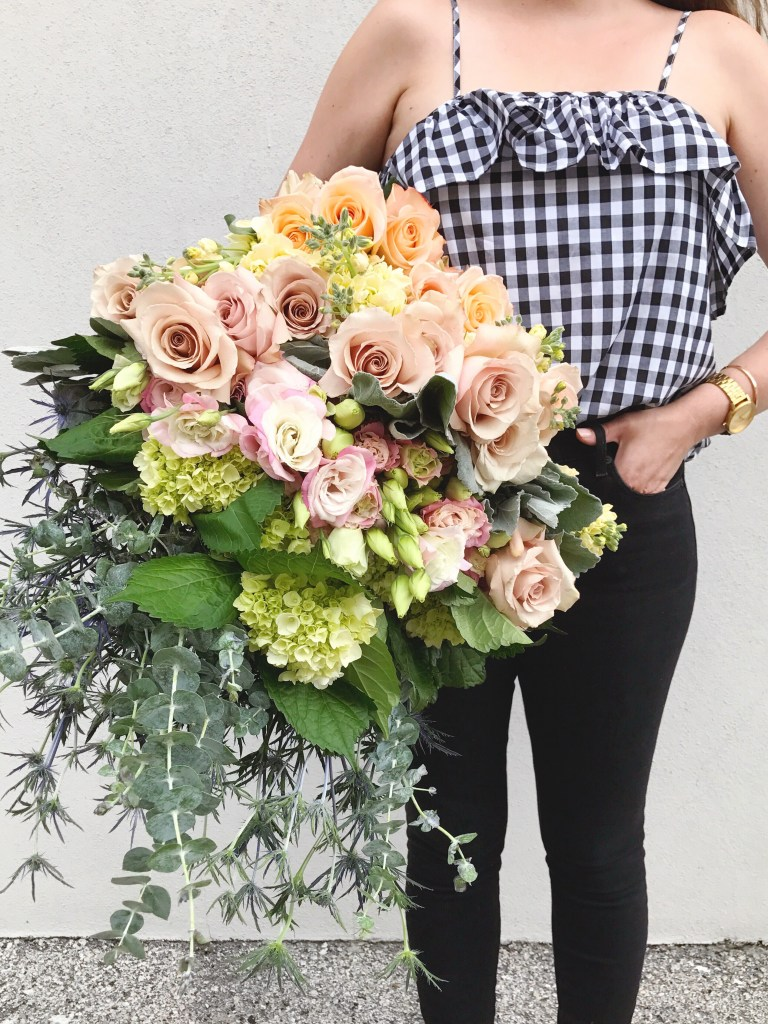 Florist in gingham camisole holding a large bundle of fresh flowers including roses, hydrangea, fresh eucalyptus, dusty miller, stock flower and blue thistle.