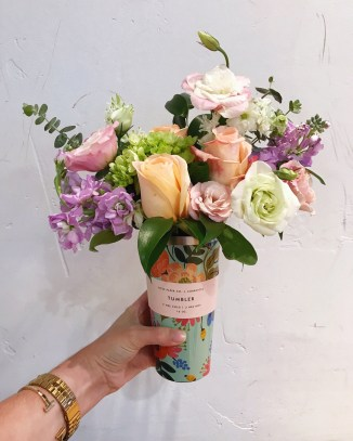 Rifle Paper Co. x Corkcicle 'Lively Floral' tumbler filled with fresh flowers, including peach roses, pink lisianthis, green hydrangea and lavender stock.