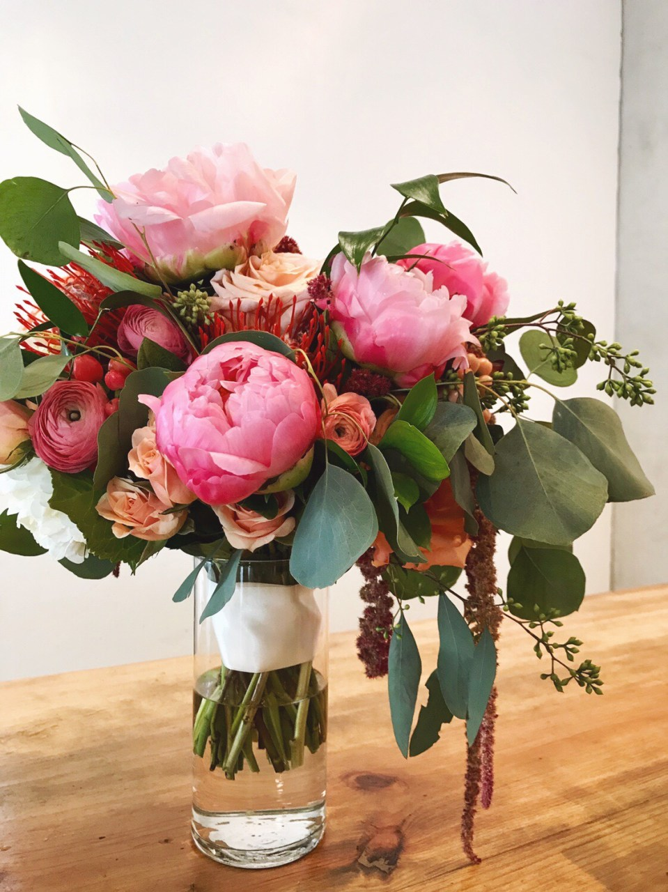 Hand-tied bridal bouquet with pink peonies, peach rananculus and assorted fresh eucalyptus