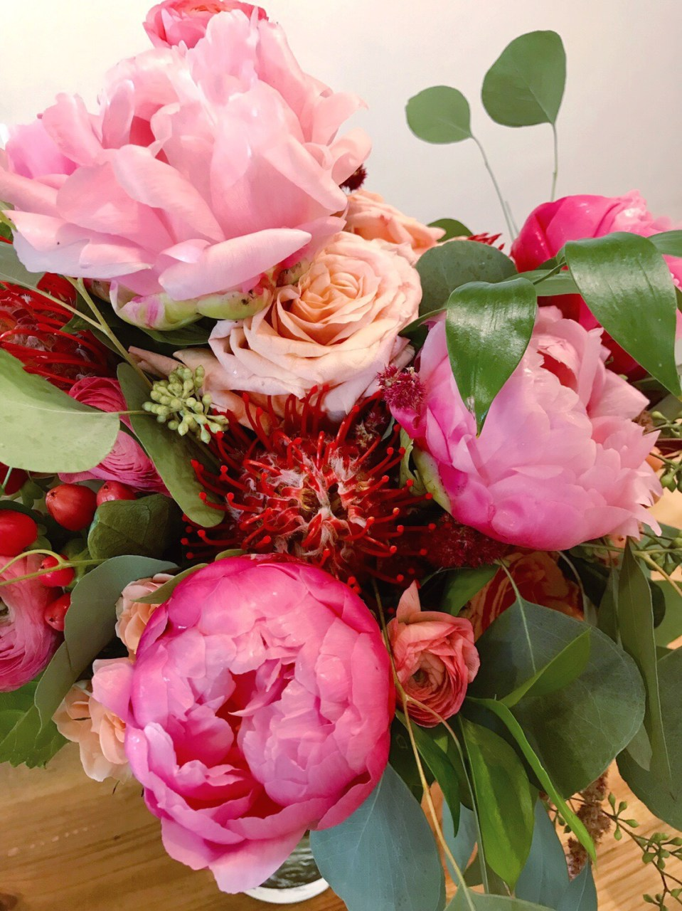 Closeup of bridal bouquet with pink peonies, peach roses and ranunculus, red pin cushion protea, and assorted fresh eucalyptus