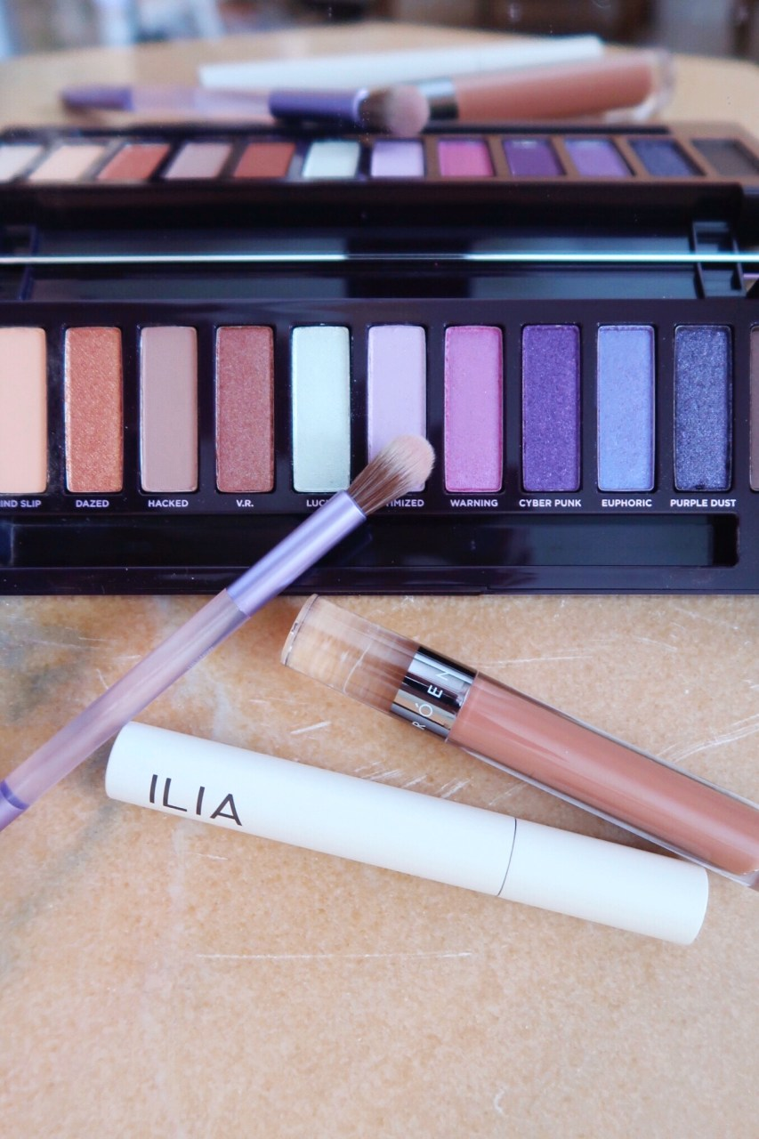 Urban Decay Ultraviolet Eyeshadow Palette, Roen Liquid Lip Balm, Ilia mascara.