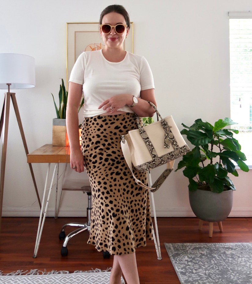 Style blogger wearing leopard midi skirt with ivory t-shirt and summer canvas bag