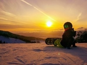 child snowboarder watching sunset