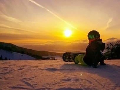 child snowboarder watching sunset