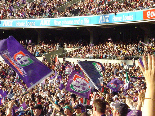 A photograph af Fremantle Dockers' supporters waving their flags.
