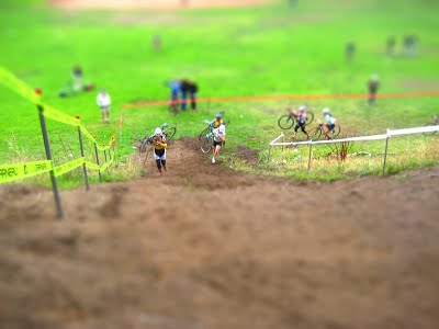 A tilt shift picture of two cyclo cross riders about to climb a hill