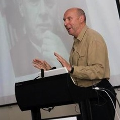 A picture of me presenting with a picture of Marshall McLuhan in the background