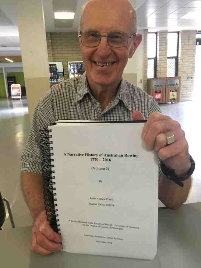 Robin Poke holding his PhD Submission