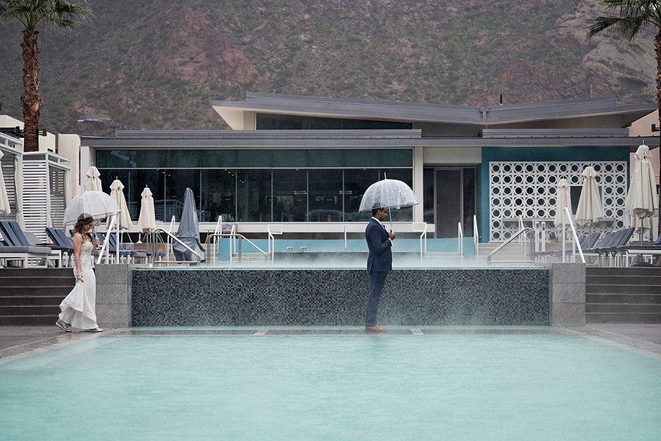 first look by a swimming pool on a rainy wedding day