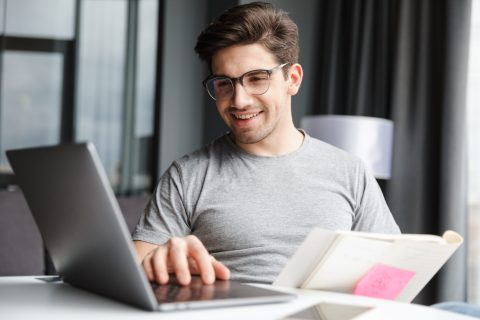Optimistic young man using laptop computer