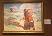 """Warren E Rollins, 'The Burden Bearers', 1929, oil on canvas, at Booth Western Art Museum, Cartersville, GA. Photo credit Kelise Franclemont. The card reads: 'Rollins gained recognition as an Indian painter in California, and is also known for helping to establish an art colony in Santa Fe in the early 1900s. This painting is very similar to a frequently copied photograph of the time, entitled, """"Carrying water to Tewa""""...'"""