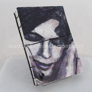 handsewn journal, exposed binding, portrait detail, woman's face, black, purple, greys; black cord closure with beads