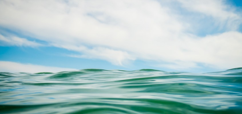 Close-up photograph of ocean wave against the blue sky