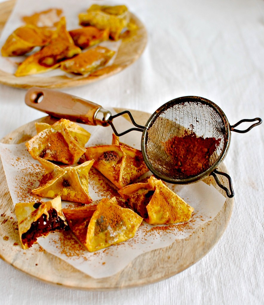 Baked Chocolate Wontons  Most recipes of this ilk call for frying. This is so not necessary! Who needs the added complication and calories of frying when baking is just as good. A great little after dinner nibble. Make them up ahead of time and keep in an air-tight container, baking just before you wish to enjoy them.  50g (1/2 cup) pecans, toasted in 180C/350F oven for eight minutes 1 heaped tbsp raw cacao powder or best-quality cocoa, plus a little extra for serving 2 pitted Medjool dates OR 3 Deglet Nour dates 2-finger pinch of salt ½ tsp vanilla powder or extract 1 tbsp coconut oil, as liquid OR milk {plant or dairy} 12 small wonton wrappers, with a few more just in case Palmful of evenly chopped dark chocolate Extra liquid coconut oil or melted butter/rapeseed oil for brushing wontons  Preheat the oven to 180C/350F. Line a baking tray with parchment/wax paper {preferably unbleached}.  Put everything but the dark chocolate and extra coconut oil in a food processor or blender {I use my Froothie}, and blend until smooth or almost smooth – your choice.  Spoon a teaspoon of the mixture into each wonton and top with a piece of chocolate. Brush a little water around the outer edge and pull edges over to make a triangle, or make other shapes if you like. I made a variety of shapes for you to choose from: 'purse', cylindrical and triangles.   Brush each wonton with melted coconut oil, rapeseed oil or melted butter and place on the lined baking tray and bake in the oven for 10 minutes.  Serve hot with extra cacao powder, or a mix of cacao and unrefined icing sugar. Spices such as cinnamon, cardamom and even five-spice are all lovely to add to either the wontons or in the dusting garnish.  Note: A serving would be three-four wontons per person.  Variation: use a small banana instead of dates  Quick variation: halve dates and place a piece of chocolate and pecan on each half; wrap in a wonton and bake!
