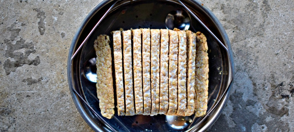 Sliced tempeh to be steamed before briefly marinating and griddling.
