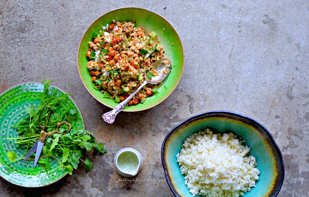 "Use your blender and one simple trick to zap whole cauliflower into perfect ""rice"" for this throw together summer tabbouleh bowl.  Add in harissa chickpeas, pre-cooked quinoa, herbs, veggies and a creamy feta and mint dressing for a cool but slightly spicy lunch or supper. Picnic-perfect and lunchbox-luscious, too."