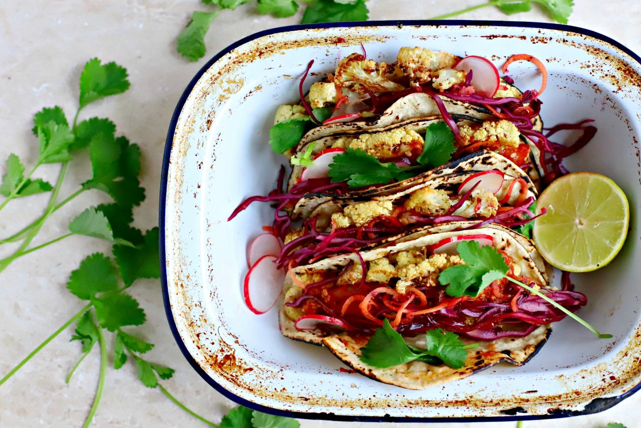 Steak-spiced #cauliflower stuffed into charred tortillas and topped with a sesame-chipotle #salsa and pomegranate-cabbage slaw. Make some for a light supper, or as part of a bigger buffet of #Mexican dishes. #vegan #tacos