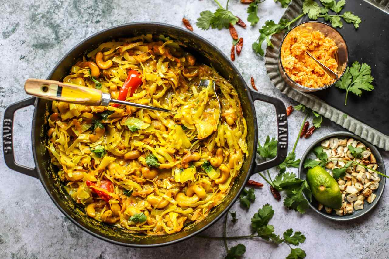 An easy-to-make, Sri Lankan-inspired mild #curry of thinly sliced #cabbage, toasted cashews, spices and coconut milk, topped with a deliciously spicy #coconut and lime sambal. A naturally #vegan and whole food #recipe.