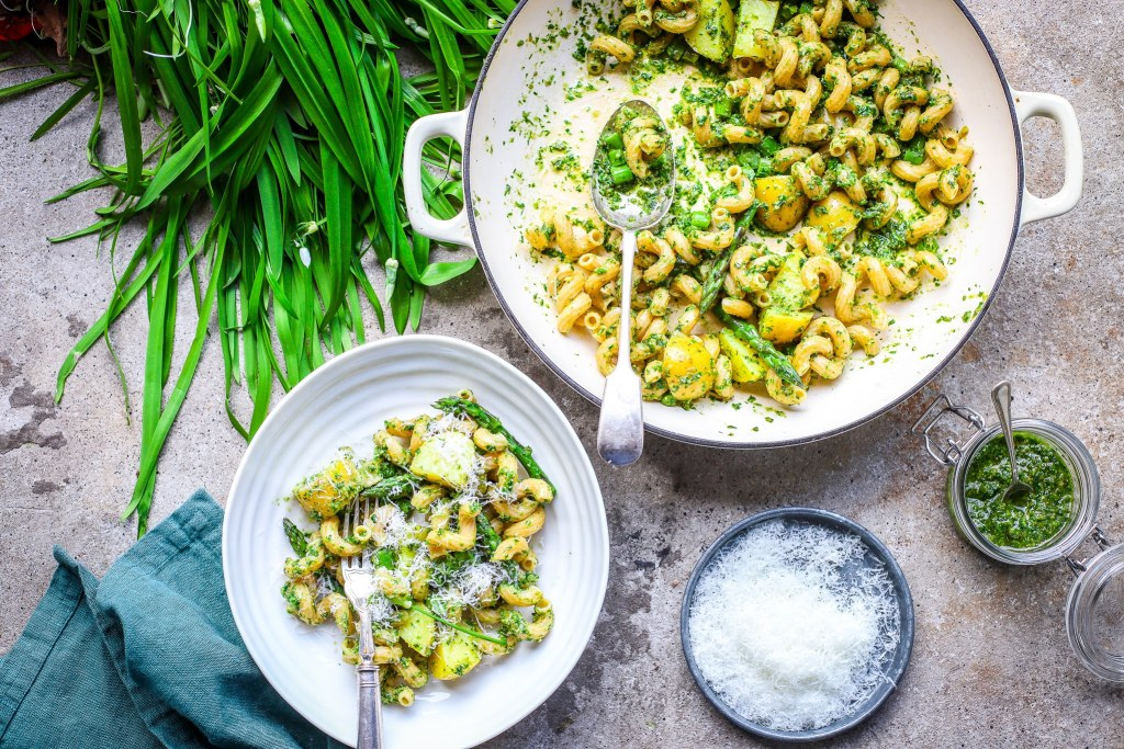 Pesto pasta with potatoes and asparagus served from a white shallow pan with filled bowl and green leaves and grated cheese on metal shallow plate