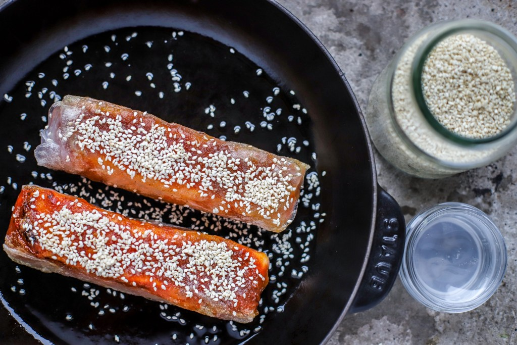 Pressing sesame seeds onto the pan-seared salmon parcels before placing in a hot oven.