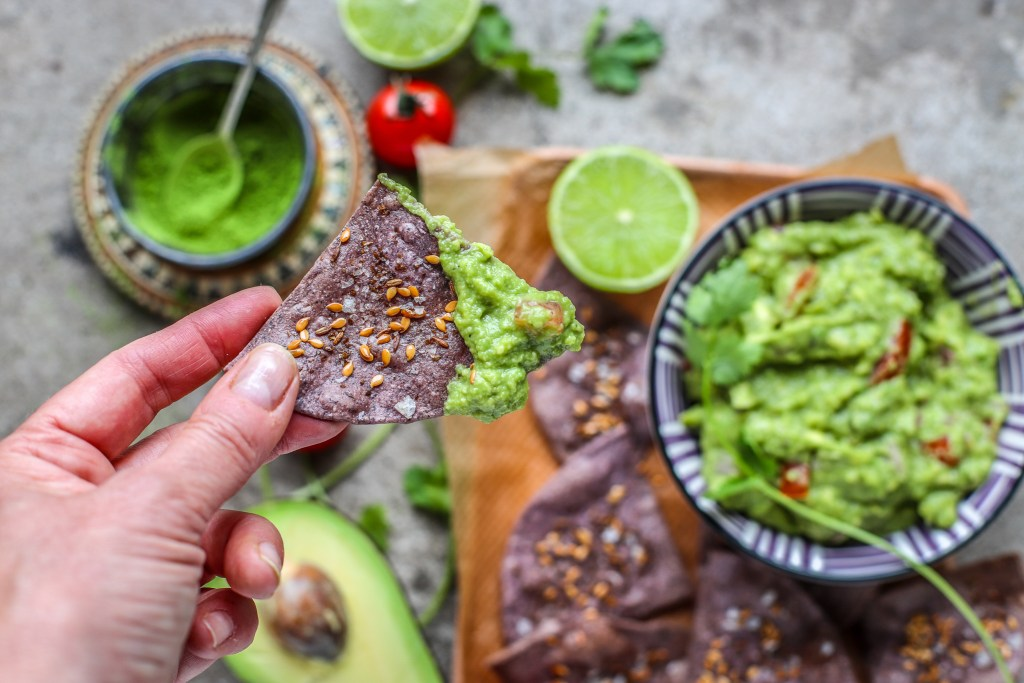 guacamole with hand holding purple tortilla chip with bit of guacamole on it