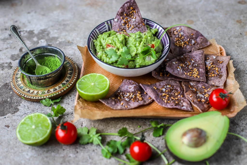 landscape image of green tea guacamole with homemade tortilla chips and fresh ingredients