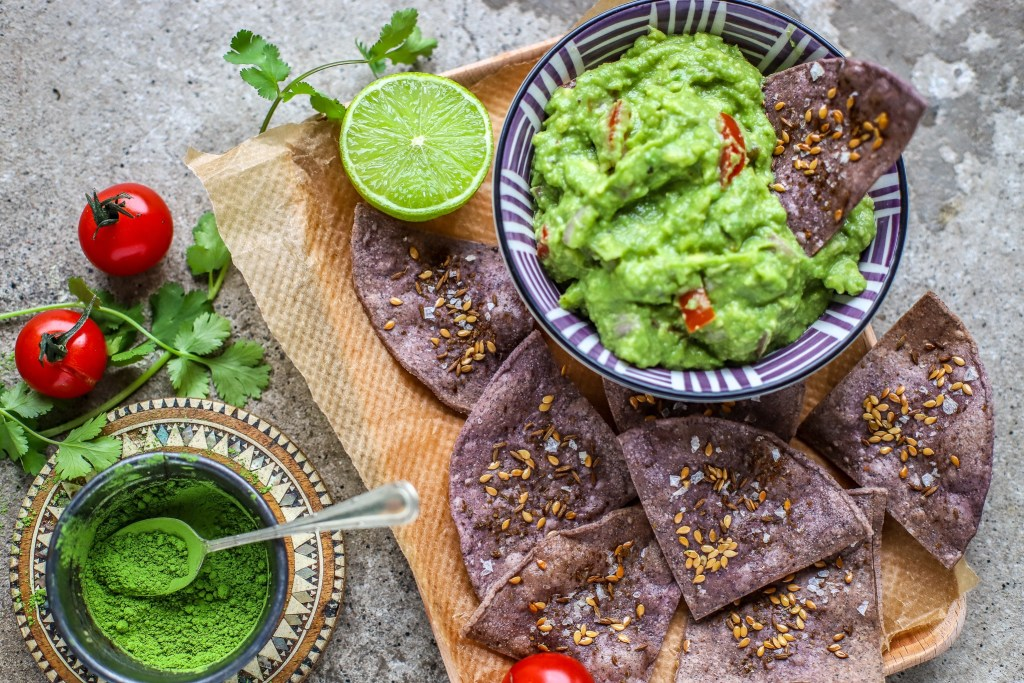 matcha guacamole in small bowl with purple tortiall chips, lime halves and matcha tea powder in tiny bowl alongside