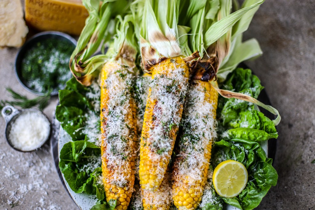 close up of buttery grilled corn with cheese and herbs